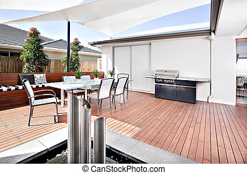 Outside relaxing area of a modern house or hotel that has a wooden floor and a grill cabinet for outdoor cooking