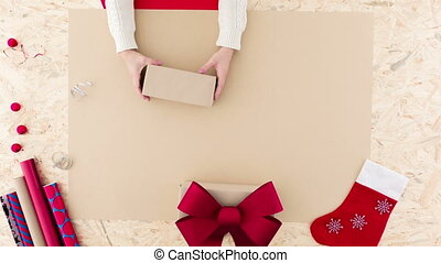 Female wrapping christmas gift - Video with woman wrapping...