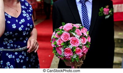 Groom Holds Wedding Bouquet of Pink Roses - groom holds...