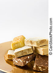 Christmas nougat on a golden plate isolated on white...