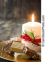 Christmas nougat and white candle on a golden plate