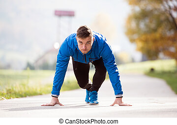 Young runner in park on asphalt path in steady position -...