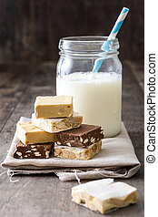 Christmas nougat and milk on wooden background