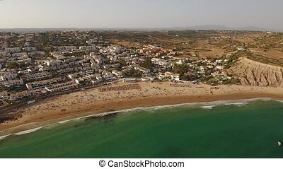 Aerial. Movies with tourists on the beach sky Luz. Portugal...