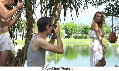 Beautiful model posing for male photographers during outdoor...