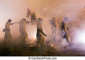 Night religious procession under full smoke of firecrackers...