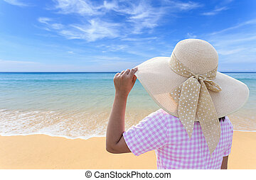 Woman with big hat stand on the beach