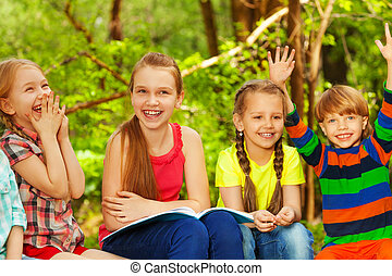 Four cute kids having fun in the summer forest