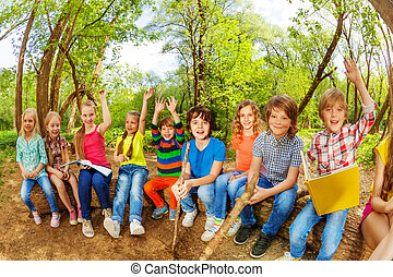 Funny kids sitting on log outdoor and reading book - Big...