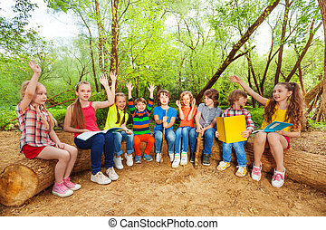 Cute kids reading books outdoor sitting on the log - Big...