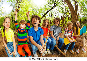 Happy kids sitting on a log and reading books - Big group of...