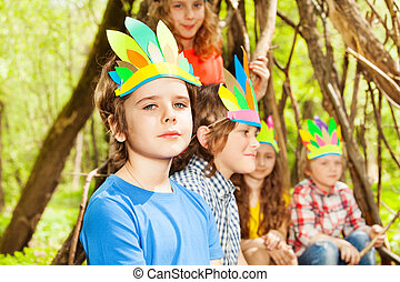 Cute boy in Injun's headdress playing with friends -...