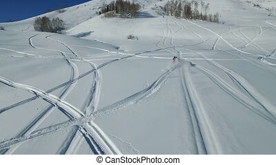 Snowmobiles charges down a mountain in powder snow, Altay...