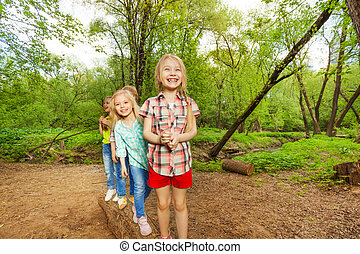 Kids standing on a log one after another in forest -...