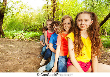 Cute happy kids sitting on a log in the forest - Five happy...