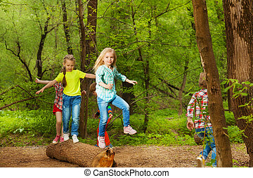 Happy kids balancing standing on the log in forest -...