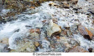 Water flows over the rocks from the camera. Valley...