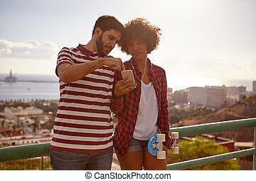 Young couple leaning on bridge railing