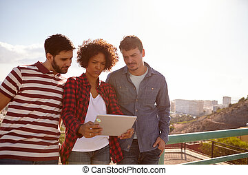 Three young millennials looking at tablet - Three young...