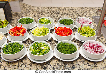 Salad bar with various sliced fresh vegetables and other...