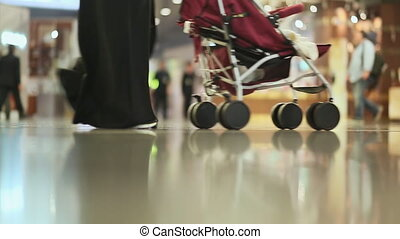 Passengers dragged baggage walking on the way at airport. Only legs view 2.