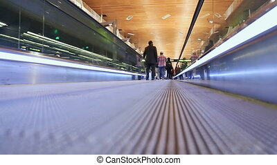 Moving sidewalk at an airport with people.