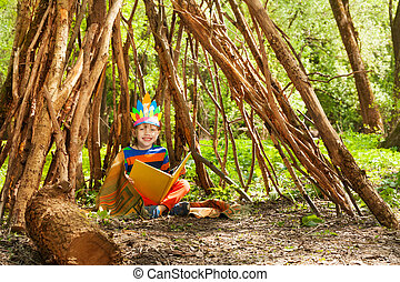 Happy boy reading stories of Red Indians in wigwam - Happy...