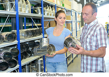 Man and woman in hardware store looking at metal flues