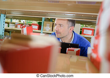 View from shelf of man selecting product