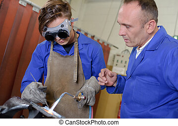 Apprentice using blowtorch, being supervised
