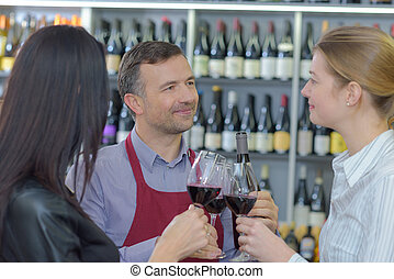People sampling red wine in liquor store