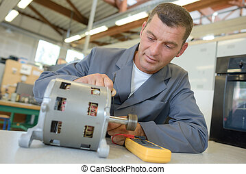 Repairman working on cylindrical electrical component