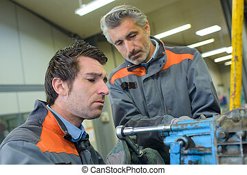Two middle aged mechanics at work