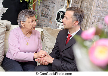Suited man holding hands of elderly lady