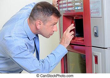 Man peering inside drinks machine