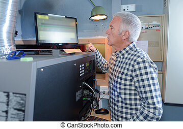 Man looking at computer screen on machine