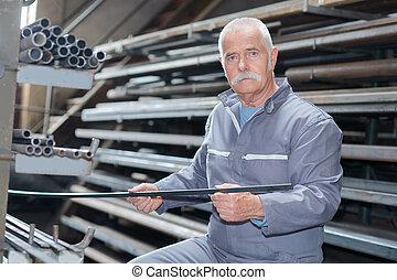 Senior man holding sheet of metal