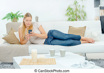 Lady layed on couch, using cellphone