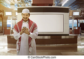 Asian muslim man holding phone - Young asian muslim man....