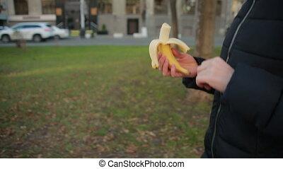 Girl eats fruit on the street