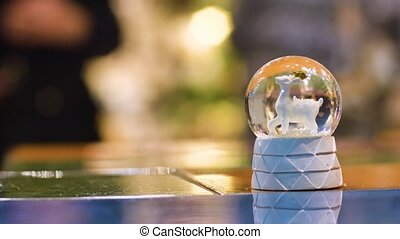 Christmas snow globe with a deer inside shakes and puts on...
