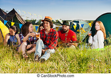 Happy young people drinking together at campsite