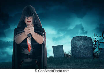 Young asian witch woman holding bloody knife on cemetery in...