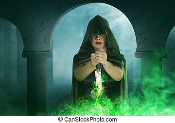 Asian witch woman holding knife with green light magic in...