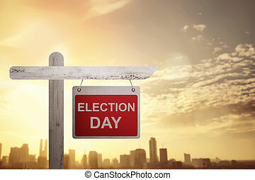 Election Day announced sign on wooden pole with city...