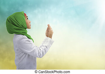 Young muslim asian woman praying to god, with hijab style,...