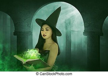 Asian witch woman holding the book of magic, the green light...