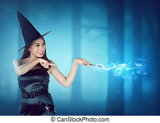 Beautiful young witch pointing and conjure something in the...