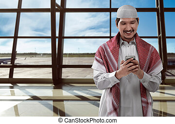 Asian man muslim on airport - Asian muslim man holding phone...