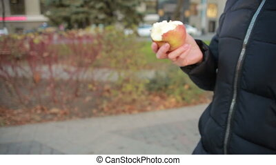 Girl eats fruit on the street - girl eating an apple...